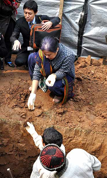 An official collects remains dug out from the Guwahati war cemetery