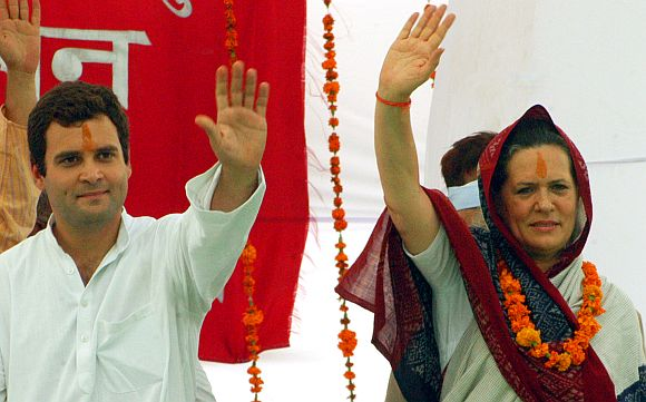 Rahul Gandhi and Congress president Sonia Gandhi wave to supporters during a rally in Rae Bareli