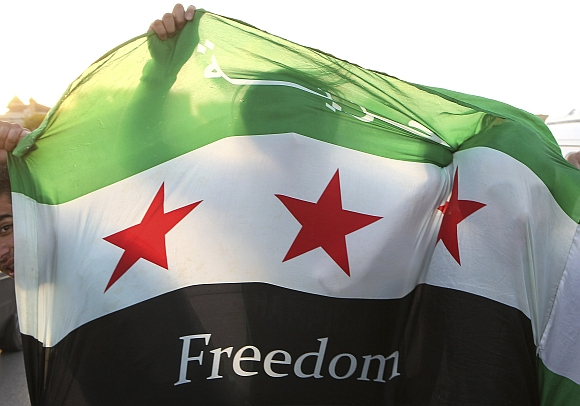 Syrian refugees and local residents holding the Syrian opposition flag take part in a demonstration against Syria's President Bashar al-Assad, outside the Syrian embassy in Amman