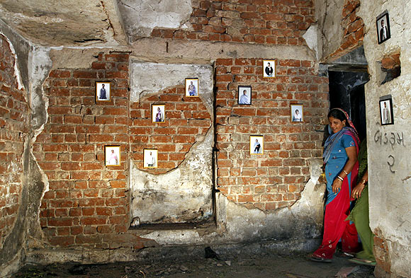 A survivor stands next to pictures of her family members inside her house that was burnt and damaged during the Gujarat riots in 2002