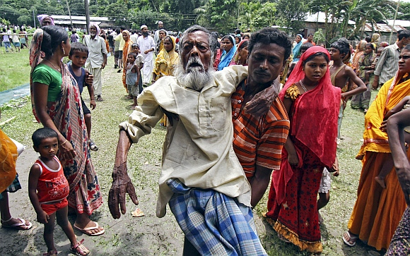 Jahar (centre), a 105-year-old villager affected by ethnic riots, is carried by his son to a relief camp near Bijni