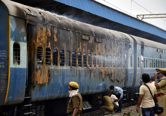 A burnt carriage of a passenger train is pictured at the Nellore railway station, Andhra Pradesh