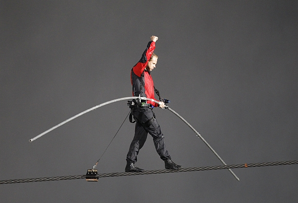 Nik Wallenda pumps his fist as he reaches the end of his tight rope walk