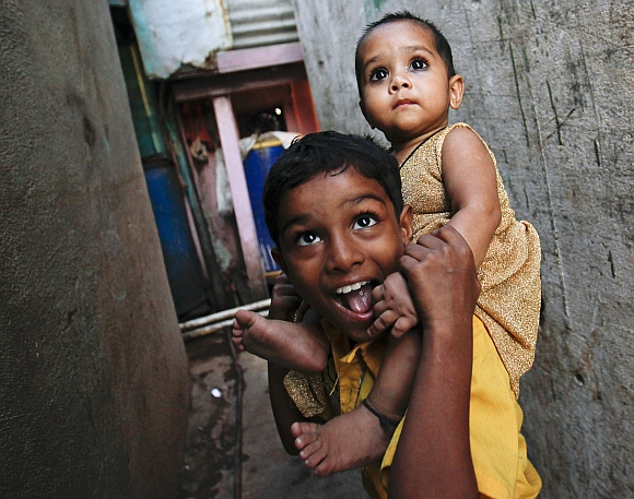 Saeed, 10, carries his nine-month-old sister Muskaan through an alley in Dharavi, one of Asia's largest slums, in Mumbai