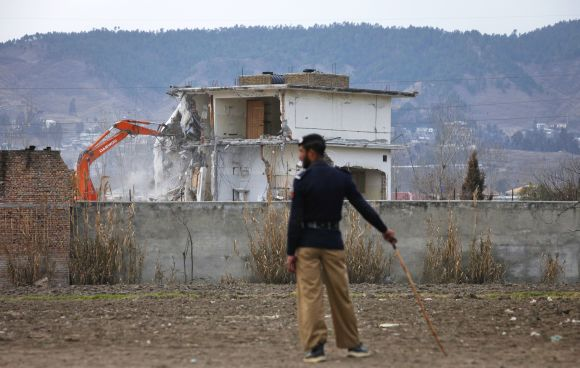 A policeman looks on as the building where bin Laden was killed is demolished in Abbottabad