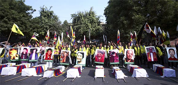 Tibetan exiles holding portraits of protesters, who were killed during demonstrations in China's Sichuan province, stand behind mock coffins during a protest in New Delhi