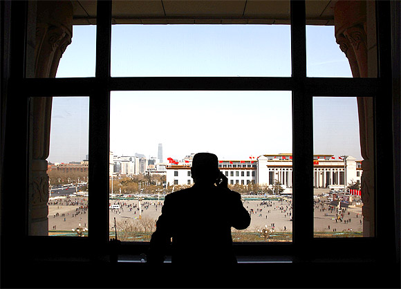 A security guard looks over Beijing's Tiananmen Square from inside the Great Hall of the People before the start of the meeting between the Tibetan provincial delegation and representatives from the National People's Congress in the Tibet Room