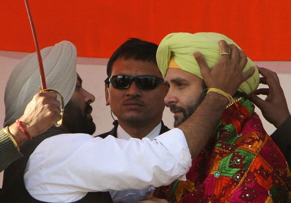 Rahul Gandhi is presented with a turban by his party supporters during a campaign rally ahead of assembly elections at Sirhind in Punjab