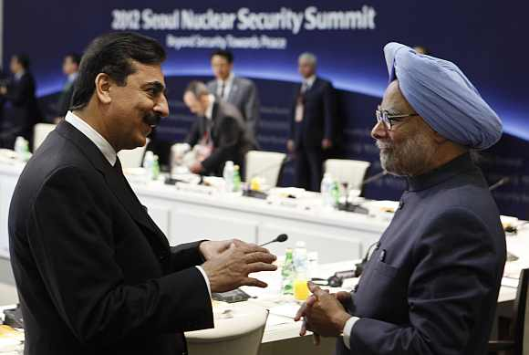 Pakistan's Prime Minister Yousuf Raza Gilani  speaks to Prime Minister Manmohan Singh during the Nuclear Security Summit in Seoul