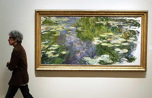 A man walks past Le Bassin aux Nympheas during a preview of Sotheby's Impressionist & Modern Art auction in New York