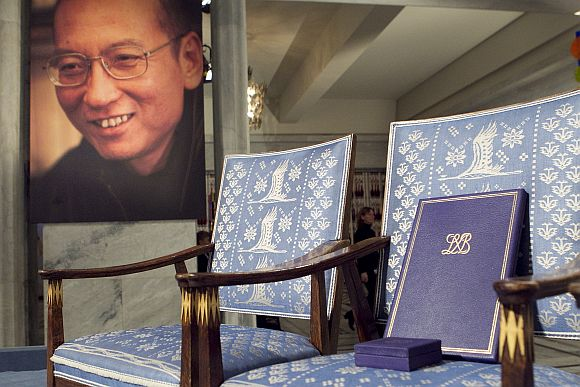 The Nobel certificate and medal is seen on the empty chair where 2010's Nobel Peace Prize winner jailed Chinese dissident Liu Xiaobo would have sat, as a portrait of Liu is seen in the background, during the ceremony at Oslo City Hall December 10, 2010