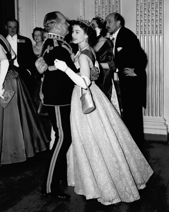 Queen Elizabeth II dancing with Air Marshal Sir John Baldwin (1892 - 1975), colonel of the 8th Hussars, at a ball held at the Hyde Park Hotel, London. The ball celebrates the centenary of the Battle of Balaclava. Photo taken on November 26, 1954