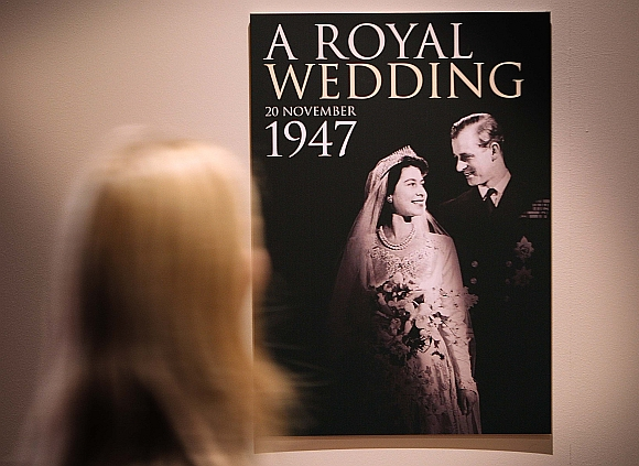 A worker looks at a poster of the 'Royal Wedding: 20 Novermber 1957 exhibition' at Buckingham Palace on July 27, 2007 in London. Queen Elizabeth II will be the first reigning sovereign to celebrate a 60th wedding anniversary