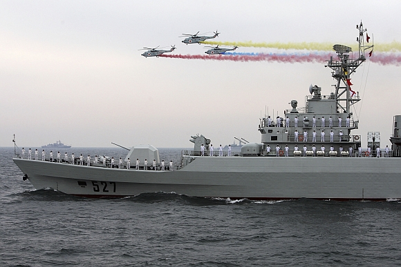 Helicopters fly past the Chinese Jiangwei II class naval frigate Luoyang at an international fleet review to celebrate the 60th anniversary of the founding of the People's Liberation Army Navy in Qingdao, Shandong province