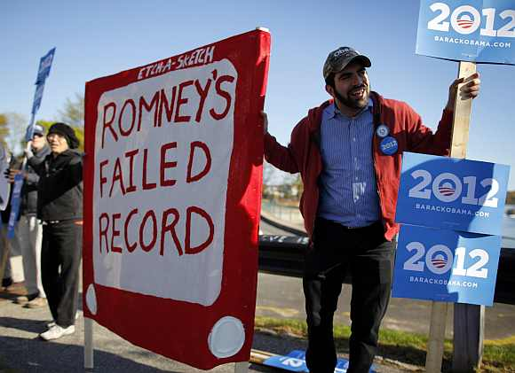 Supporters of US President Barack Obama demonstrate before a campaign stop by Republican presidential candidate and former Massachusetts Governor Mitt Romney in Portsmouth, New Hampshire
