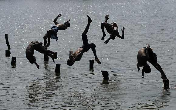 Boys jump in a pond to cool off in Agartala