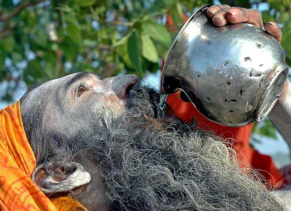 A sadhu drinks water to beat the heat in Allahabad