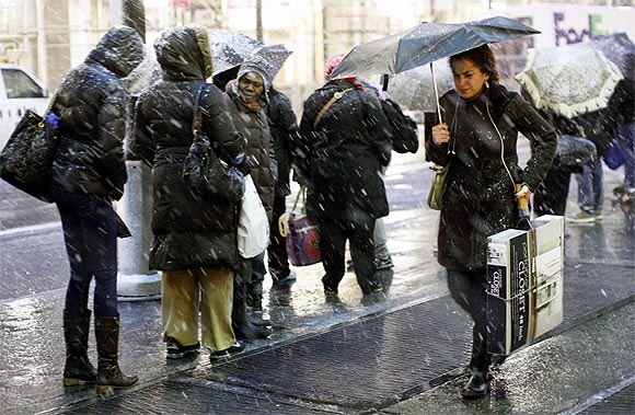 eople wait at a bus stop during a snow storm in New York on Wednesday