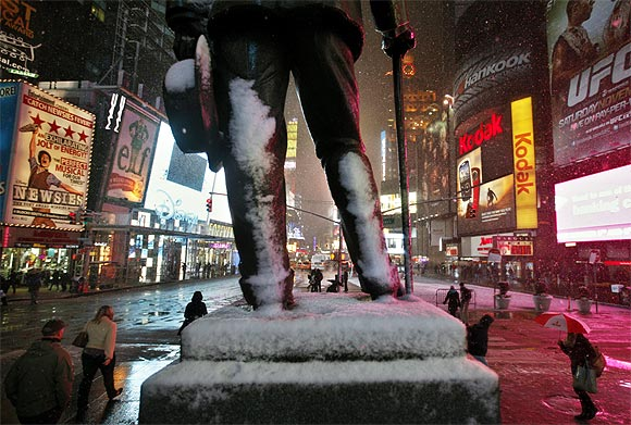 Snow gathers on the statue of George M Cohan in New York's Times Square