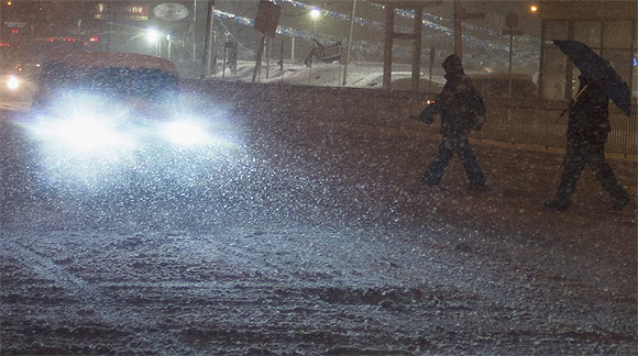 Pedestrians walk through a snow storm in the Staten Island borough of New York