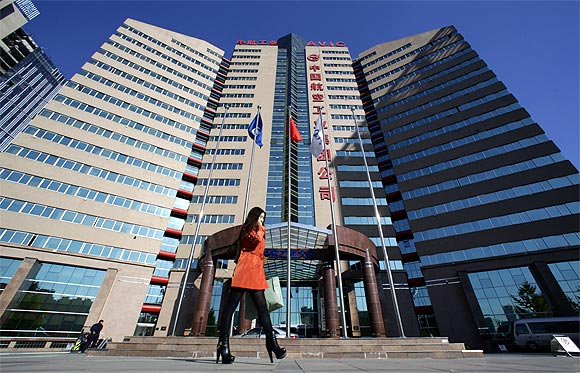 A woman walks past the Aviation Industry Corporation of China headquarters building in Beijing