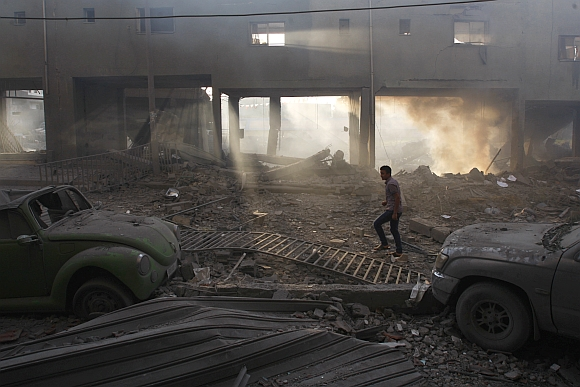 A Palestinian inspects the damage to a soccer stadium after an Israeli air strike in Gaza City