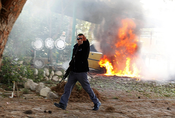 An Israeli police officer gestures in front of a burning car after a rocket fired by Palestinian militants in Gaza landed in the southern city of Ashkelon