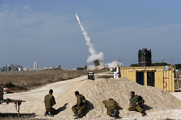 Israeli soldiers watch as an Iron Dome launcher fires an interceptor rocket near the southern city of Ashdod