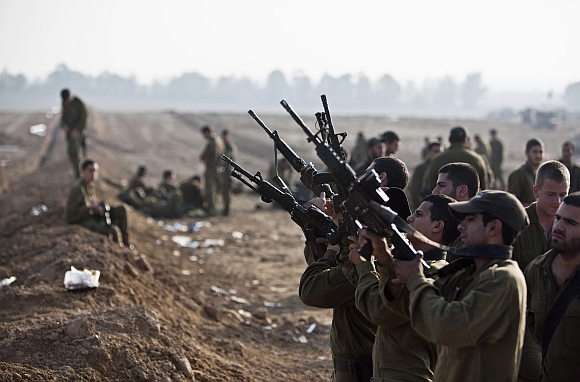 Israeli soldiers check their weapons at a staging area near the border with the Gaza Strip