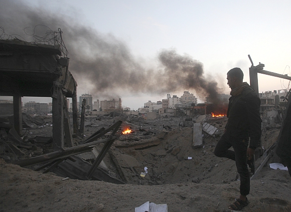 A Palestinian walks past a destroyed Hamas security site after an Israeli air strike in Gaza City