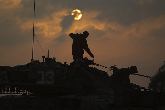 Israeli soldiers prepare a tank near Israel's border with the central Gaza Strip