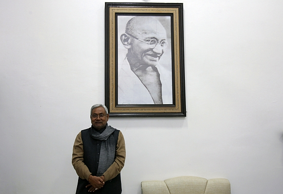 Bihar's chief minister and leader of Janata Dal United party Nitish Kumar poses in front of a portrait of Mahatma Gandhi