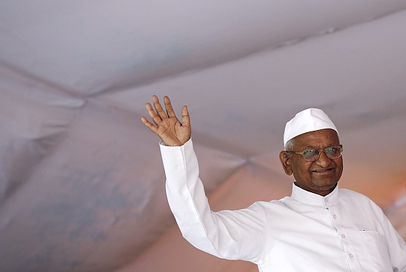 Anna Hazare waves to his supporters during his public hunger strike in New Delhi
