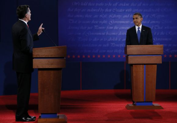Republican presidential nominee Romney speaks as President Obama listens during the first presidential debate in Denver