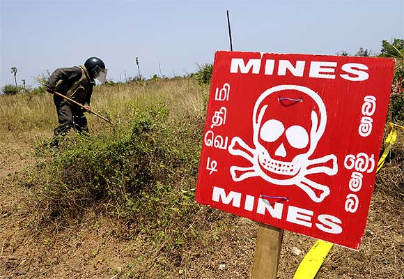 A Sri Lankan soldier looks for mines to clear near a road, which was recently re-opened, between Kandy and Jaffna, in northern Sri Lanka