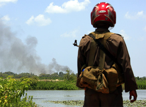 A soldier looks across to a trail of smoke coming from inside the 'No Fire Zone' near Putumatalan town located in northern Sri Lanka