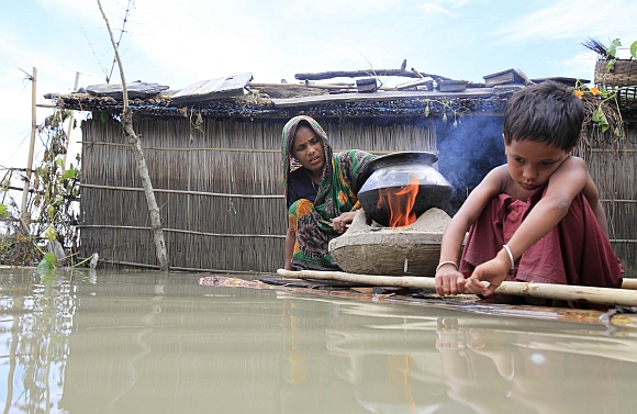 A woman cooks next to her child on a makeshift banana plant raft at a flooded village in Kurigram, Bangladesh