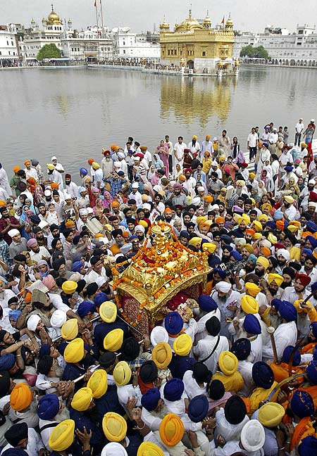 Sikh devotees carry the Guru Granth Sahib in a palanquin during a religious procession inside the Golden Temple.