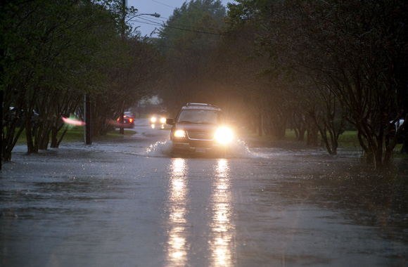 Vehicles make their way through flooded streets as the effects of wind and rain from Hurricane Sandy hit Virginia Beach, Virginia,