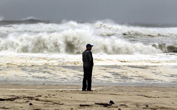 A man stands on the beach to watch the storm surf, kicked up ahead of Hurricane Sandy, in Southampton, New York