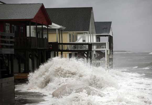 A wave crashes over the protecting sandbags in front of the houses on the east side of Ocean Isle Beach during Hurricane Sandy in Ocean Isle Beach, North Carolina