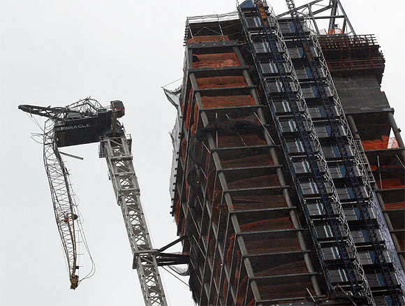 partially collapsed crane hangs from a high-rise building in Manhattan as Hurricane Sandy makes its approach in New York
