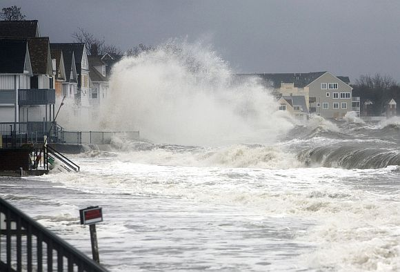 Waves crash over homes along the shoreline in Milford, Connecticut