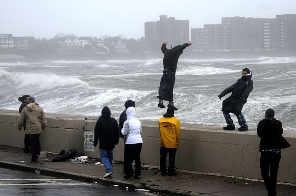 People brave high winds and waves along Winthrop Shore Drive as Hurricane Sandy comes up the coast on October 29, 2012 in Winthrop, Massachusetts