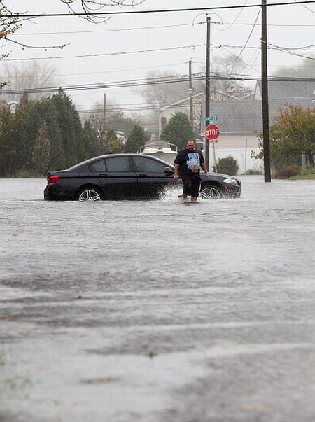 Joseph Arpaio of Massapequa abondons his car on 5th Street as high tide, rain and winds flood local streets in Lindenhurst, New York