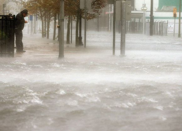 A man stands on a dry patch of sidewalk on a flooded street as Hurricane Sandy moves up the coast in Atlantic City, New Jersey