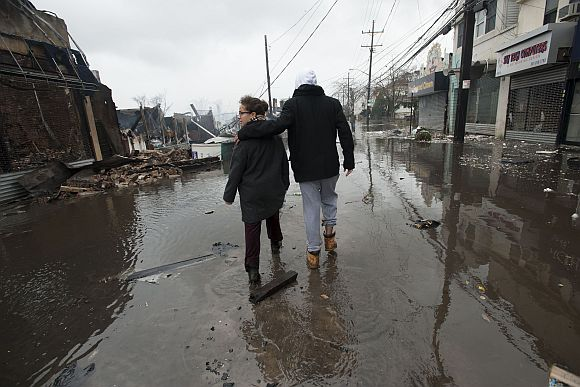 People walk through floodwaters in the Rockaways section of New York