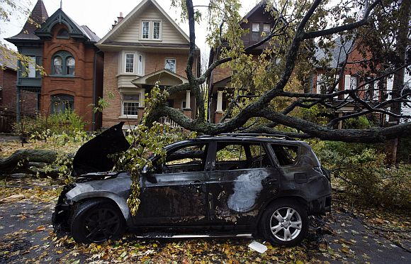 A car is seen burned out in an electrical fire after a tree fell over a power line due to the remnants of Hurricane Sandy in Toronto