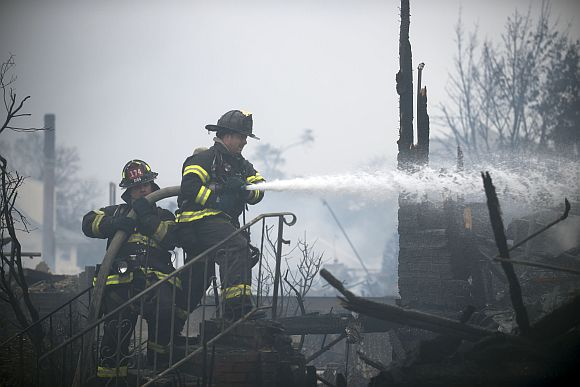 Firefighters work to extinguish a fire in the Rockaways section of New York