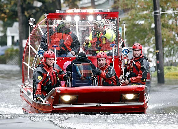 Rescue workers use a hovercraft to rescue a wheelchair-bound resident from flood waters brought on by Hurricane Sandy